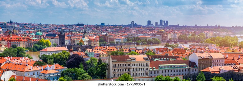 Prague red roofs and dozen spires of historical Old Town of Prague. Cityscape of Prague on a sunny day. Red rooftops, spires and the Charles Bridge and Vltava River in the background. Prague, Czechia.
