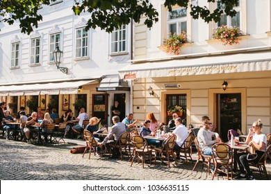 Prague, September 29, 2017: A popular street cafe near the Charles Bridge. Local residents and tourists rest, eat and communicate on a sunny warm day.