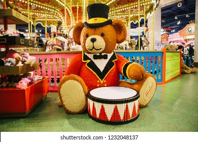 Prague September 29, 2018: A huge bear with a drum made from Lego in a toy store Hamleys. In the background is a carousel.