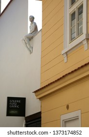 """Prague - September 6, 2014: Sculpture of a girl sitting on the roof of a building """" Galerie Foto Grafic"""""""