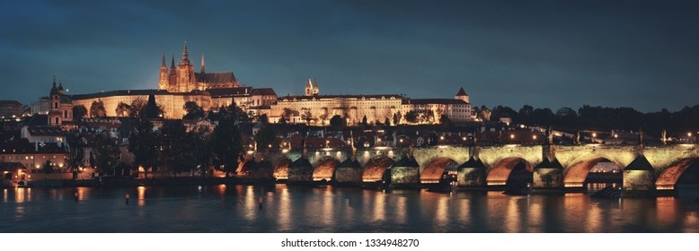 Prague skyline and bridge over river in Czech Republic at night panorama.