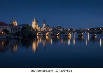 Prague skyline and bridge over river at night. Czech Republic.