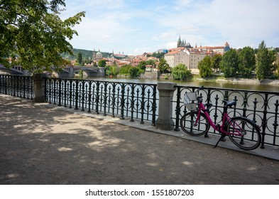 Prague, Summer 2019. View of the Prague's castle, Charles bridge and the Vltava river from the Josef Mánes park. In the foreground a pink bike rests in a rail.