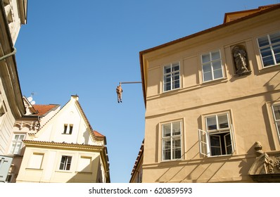 PRAGUE,CZECH REPUBLIC–APRIL 10,2017: Hanging man sculpture above Husova street by Czech sculptor David Cerny. His 1997 creation portrays a 220-centimeter Sigmund Freud hanging by one hand.