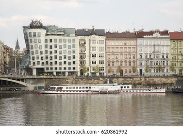 PRAGUE,CZECH REPUBLIC–APRIL 9, 2017: Riverside embankment at river Vltava. Dancing House or Fred and Ginger (Tancici dum) is a modern landmark  and was designed in 1992 and completed in 1996.