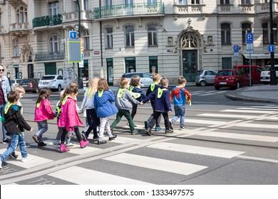 PRAGUE-CZECH REPUBLIC-APRIL-17-2018:Group Of School Children Crossing Road On Crosswalk With Traffic at Prague,Czech Republic