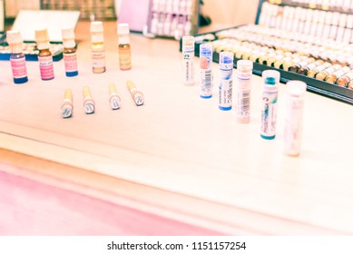 Praha, Czech Republic - June 24, 2018: Collection of diverse homeopathic remedies in glass or plastic containers on wooden pharmacy shelf. Boiron and other historical brands. Illustrative editorial.