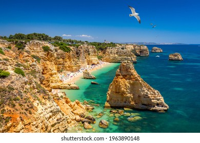Praia da Marinha, beautiful beach Marinha in Algarve, Portugal. Navy Beach (Praia da Marinha) with flying seagulls over the beach, located on the Atlantic coast in Lagoa Municipality, Algarve.