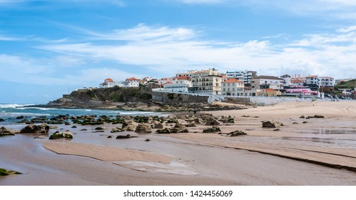 Praia das Maçãs, Portugal on a sunny summer day - a beautiful view of the beach & village, large waves and a blue sky.