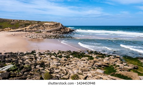Praia das Maçãs in Portugal - view of a beautiful beach and rocky coastline with large waves on a sunny summer day