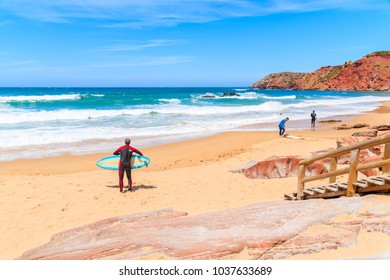 PRAIA DO AMADO BEACH, PORTUGAL - MAY 15, 2015: People surfing on Praia do Amado beach with ocean waves hitting shore. Algarve region is popular holiday destination in southern Europe.