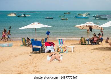 Praia do Forte, Brazil - Circa September 2019: Woman sunbathing with a thong bikini at Praia do Forte - popular beach near Salvador, Bahia