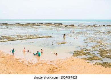 Praia do Forte, Brazil - Circa September 2019: People enjoying the natural swimming pools at Praia do Forte - popular beach near Salvador, Bahia