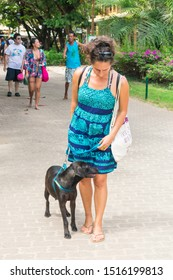 Praia do Forte, Brazil - Circa September 2019: Woman walking her dog at the main street of Praia do Forte, Bahia state (Northeast Brazil)