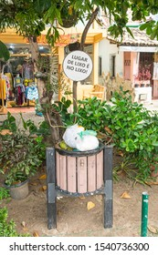 "Praia do Forte, Brazil - Circa September 2019: Trash can with a sign above written ""The place for trash is in the trash"" at Praia do Forte, popular beach resort near Salvador"