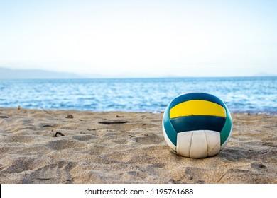 PRAIA DO JABAQUARA/ILHABELA/SAO PAULO/BRAZIL - AUGUST 8, 2018. Volleyball ball on the beach sand and sea in the background.