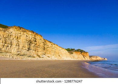 Praia do Porto de Mos, long beach in Lagos, Algarve region, Portugal. Beautiful golden beach, surrounded by impressive rock formations. Is a favourite spot for surfers and locals