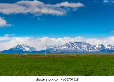 Prairie farmland and wind turbines in the shadow of the Rocky Mountains Alberta Canada