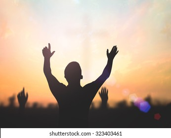 Praise and adoration concept: Silhouette human raised hands for worship God on blurred cross at sunset background