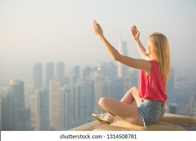 Praise and Relaxation -Young woman with arms raised to the sky sitting on top a skyscraper overlooking the city.