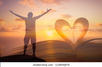 Praise and worship concept. Heart shape page from book and man standing with arms in the air facing the sunset.
