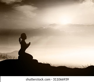 Praise and worship concept: Sepia tone, silhouette of woman kneeling and praying over beautiful sunset background.