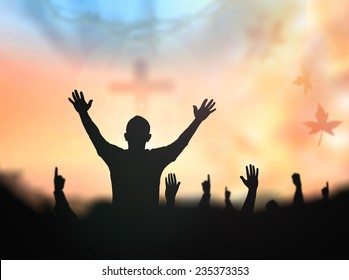 Praise and worship concept: Silhouette human raising hands to praying God on blurred cross with crown of thorn sunset background