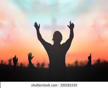 Praise and worship concept: Silhouette human raising hands to praying God on blurred cross with crown of throne sunset background.