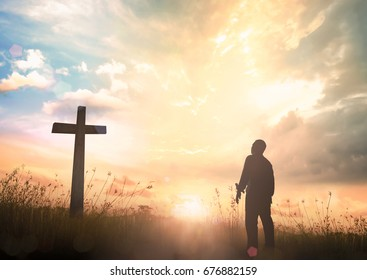 Praise and worship concept: Silhouette human standing and the cross on meadow sunset background.