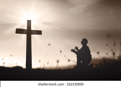 Praise and worship concept: Silhouette humble man kneeling and praying at the cross on blurred mountain sunset background.