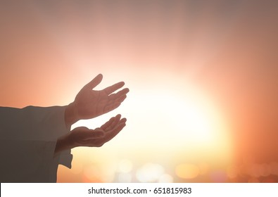 Praise and worship God concept: Prayer open two empty hands with palms up against blurred sunset background