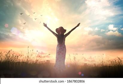 Silhouette schöne Frau hob die Hände auf Wiese-Sonnenuntergang Hintergrund