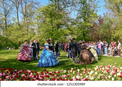 Pralormo / Italy - April 21 2018: People in costumes dancing in the blooming park of the Castle of Pralormo during the annual Mister Tulip event with tourists in spring, Piedmont