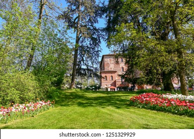 Pralormo / Italy - April 21 2018: Park of the Medieval Castle of Pralormo with ancient trees and bed of tulips in spring during Mister Tulip botanic event, Piedmont