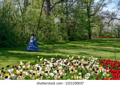Pralormo / Italy - April 21 2018: Elegant lady in nineteenth-century costume in the park of the Castle of Pralormo during Mister Tulip botanic event in spring, Piedmont