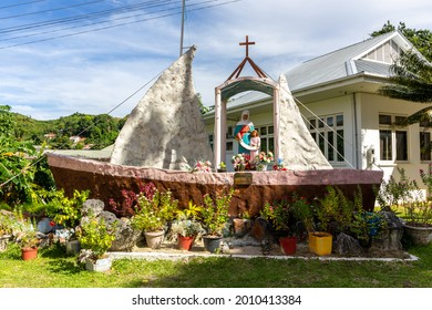 Praslin, Seychelles, 1.05.2021. Statue of Sainte Anne of Praslin standing on a boat shaped chapel outside the St Anne's Catholic Church in Baie Ste Anne with tropical vegetation around.