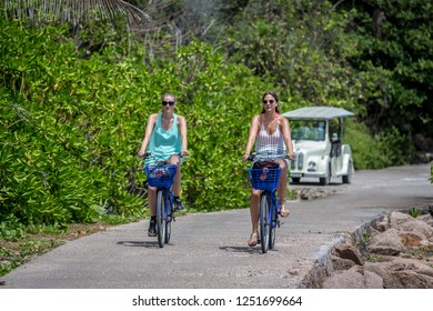 Praslin, Seychelles - Oct 21th 2018 - Two young ladies bicycling around the island of Praslin in a sunny day in Seychelles