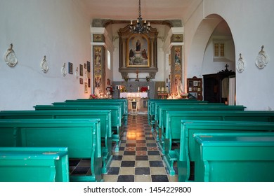 PRATO NEVOSO, ITALY - AUGUST 14, 2016: Virgin of the Snow ancient church interior with green pews on mountain top in Prato Nevoso, Italy.