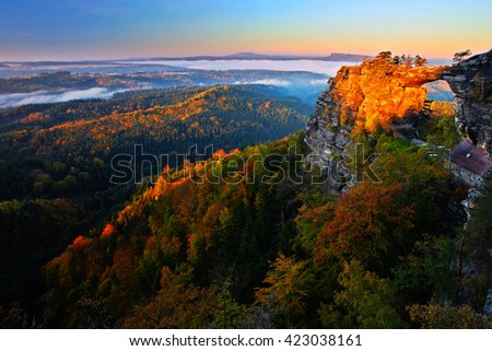 Pravcicka brana rock bridge monument in autumn colours. Czech national park Ceske Svycarsko, Bohemian Switzerland park. Autumn landscape with fog, landscape with orange trees.