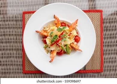 Prawn appetizer with cabbage, bell peppers and tomatoes on restaurant table, shot from above