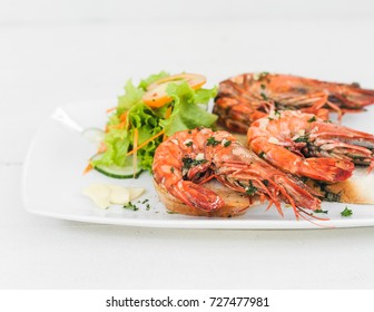 Prawn dish on the toasted bread with salad and garlic