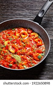 Prawn karahi - pakistani tomato shrimp curry with lime juice red chili and red curry paste served on a frying pan with fresh cilantro on a dark wooden background with linen towel, top view, close-up