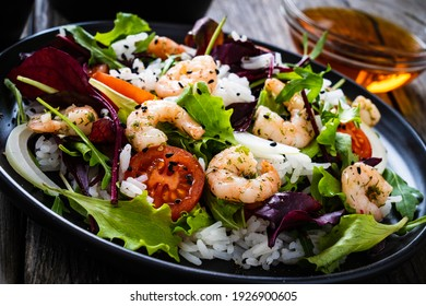 Prawn salad with white rice, lettuce, cherry tomatoes and onion on wooden background