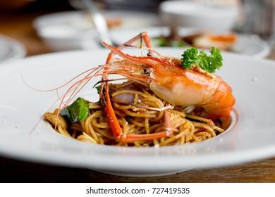 prawn spaghetti with Thai TomYum flavor on white plate