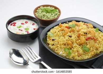 prawns biriyani -attractively arranged prawns biriyane  in a black coloured plate with onion raita and green chutny as side dish tasty kerala special biriyani - Shutterstock ID 1614853585