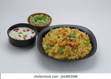 prawns biriyani -attractively arranged prawns biriyane  in a black coloured plate with onion raita and green chutny as side dish tasty kerala special biriyani - Shutterstock ID 1614853588