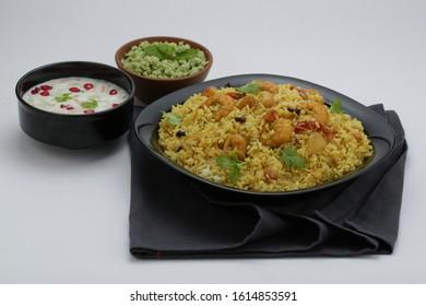 prawns biriyani -attractively arranged prawns biriyane  in a black coloured plate with onion raita and green chutny as side dish tasty kerala special biriyani - Shutterstock ID 1614853591