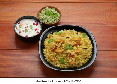 prawns biriyani -attractively arranged prawns biriyane  in a black coloured plate with onion raita and green chutny as side dish tasty kerala special biriyani - Shutterstock ID 1614854251