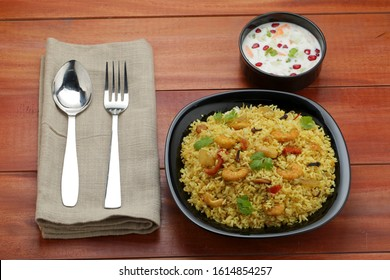 prawns biriyani -attractively arranged prawns biriyane  in a black coloured plate with onion raita and green chutny as side dish tasty kerala special biriyani - Shutterstock ID 1614854257