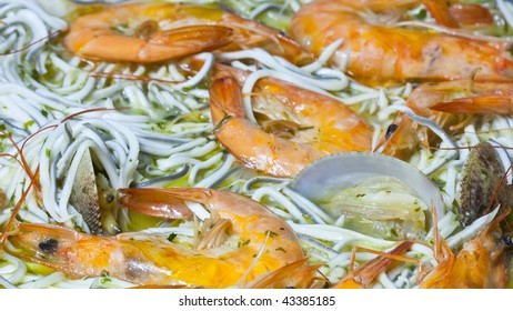Prawns, gulas and clams cooking with the bottom outside center